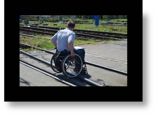Image of a man in a wheelchair crossing railroad tracks in a road: Do I understand this situation, pity the man, or sympathize that things are this way?